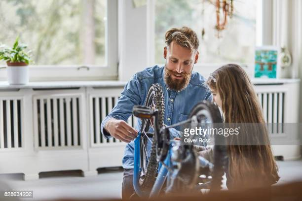 Father and daughter repairing bicycle at home