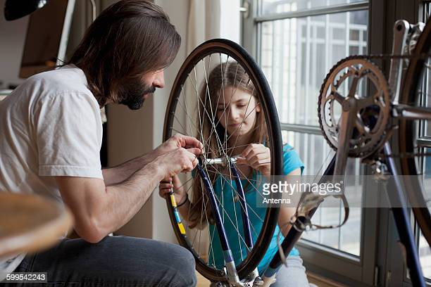 Father and daughter repairing bicycle together at home