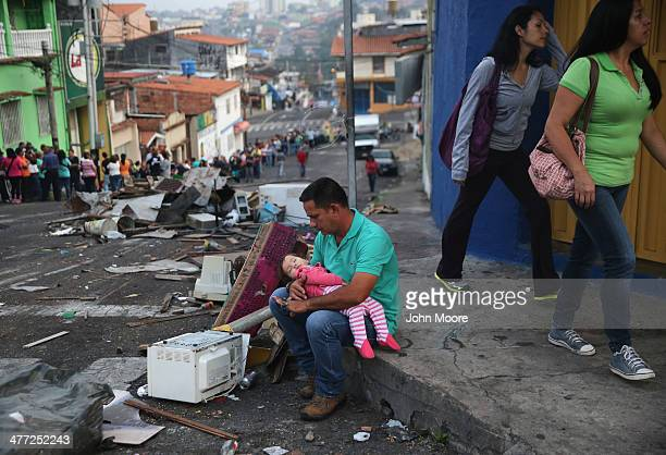 A father and daughter rest while someone holds their place before sunrise in a long line to buy basic foodstuffs at a supermarket on March 8 2014 in...