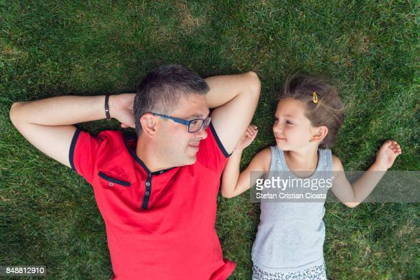 Father and daughter resting on grass