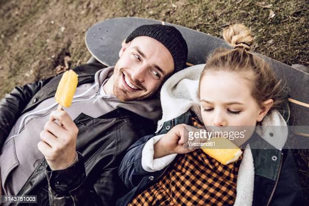 father and daughter resting on skateboard, eating ice cream - eis essen stock-fotos und bilder