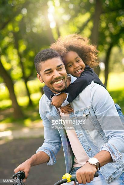 father and daughter riding a bike together. - piggyback stock pictures, royalty-free photos & images