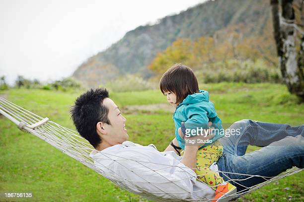 Father and daughter riding a hammock