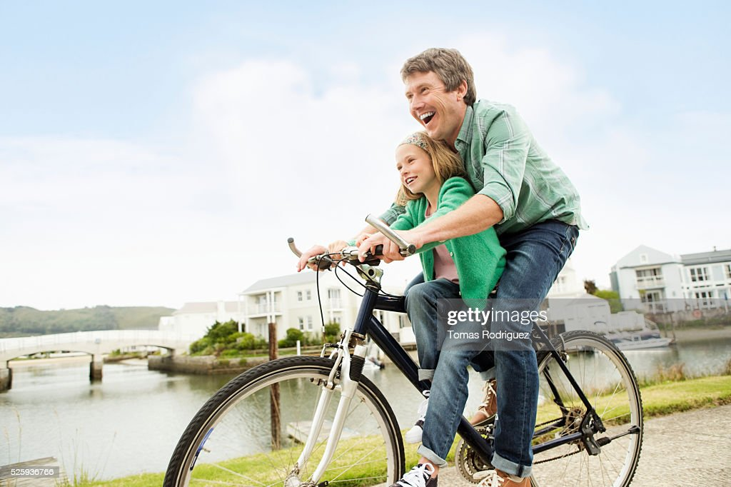 Father and daughter (8-9) riding bicycle : Bildbanksbilder