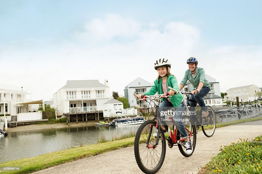 Father and daughter (8-9) riding bicycles : Foto de stock