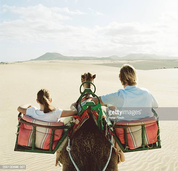 Father and daughter (8-10) riding camel, rear view
