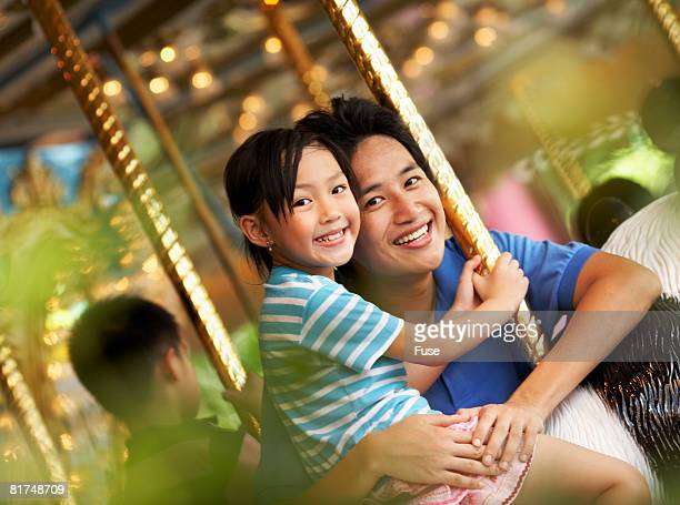 Father and Daughter Riding Carousel