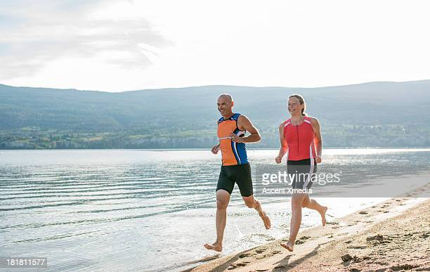 father and daughter run along lake front, beach - okanagan valley stock pictures, royalty-free photos & images