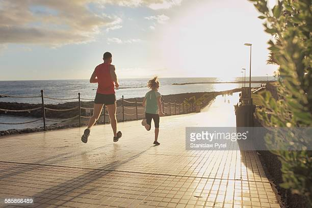 Father and daughter running near ocean
