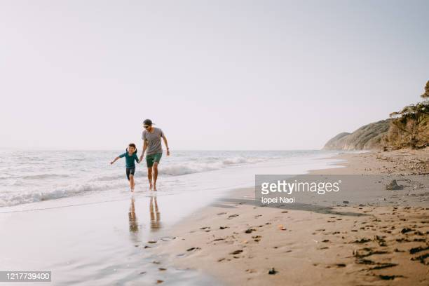 father and daughter running on beach - east asian ethnicity stock pictures, royalty-free photos & images