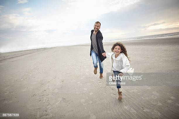 Father and daughter running on beach
