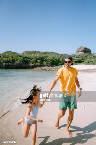 father and daughter running on tropical beach, okinawa, japan - ippei naoi stock pictures, royalty-free photos & images