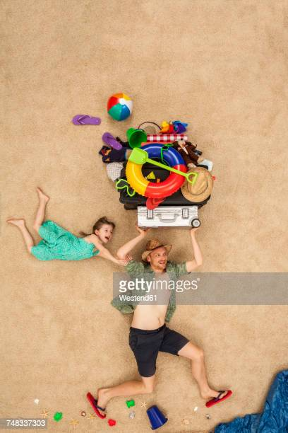 Father and daughter running to the sea, carrying beach equipment on the head