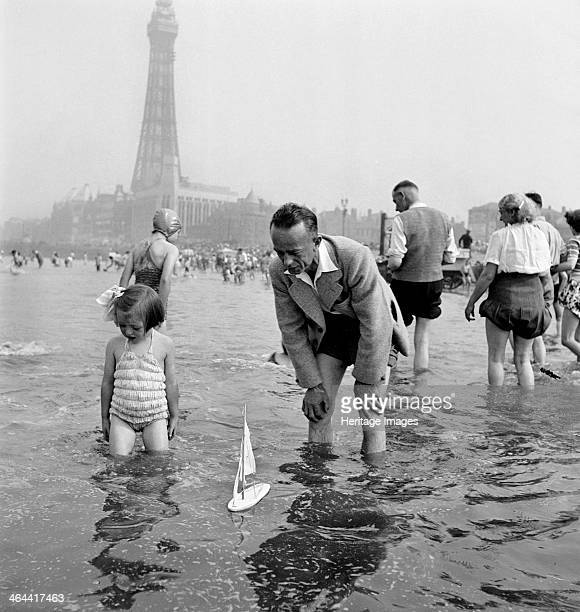 Father and daughter sail a model yacht in the sea, though the girl seems to be losing interest, Blackpool, c1946-1955. The Blackpool Tower is in the...