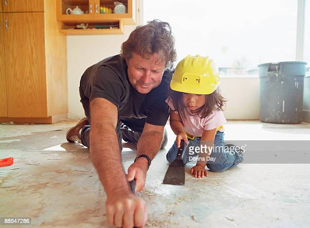 Father and daughter scraping kitchen floor