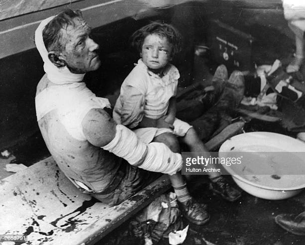 Father and daughter share a stretcher at a Warsaw first aid station. They were injured in a German air raid on a working-class district of Warsaw...