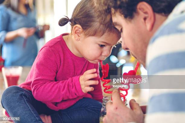 Father and daughter sharing a lemonade