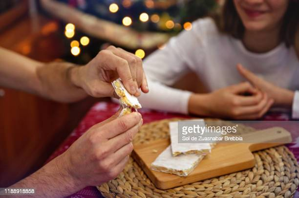 father and daughter sharing time at christmas, eating almond nougat next to the christmas tree - nougat stock pictures, royalty-free photos & images