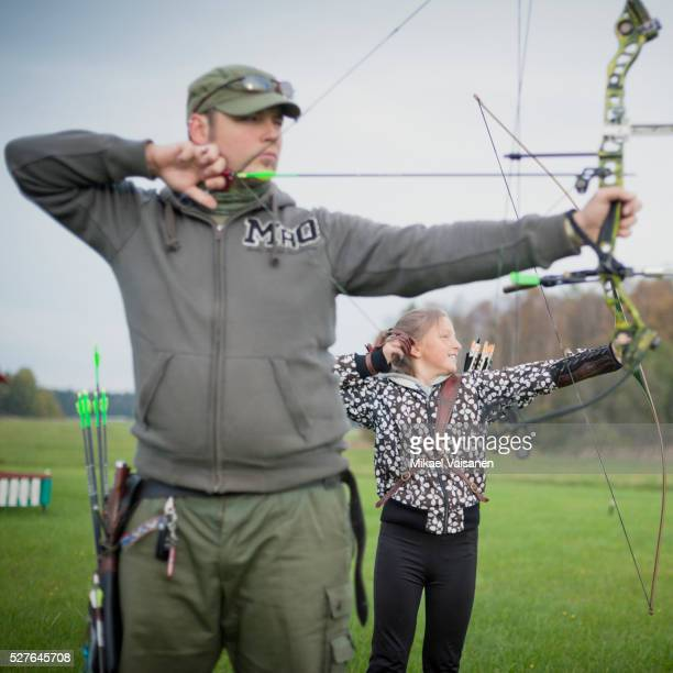Father and daughter (10-12) shooting with bow and arrow