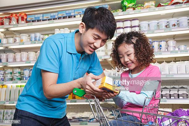 Father and Daughter Shopping in Supermarket, Looking at Juice Box
