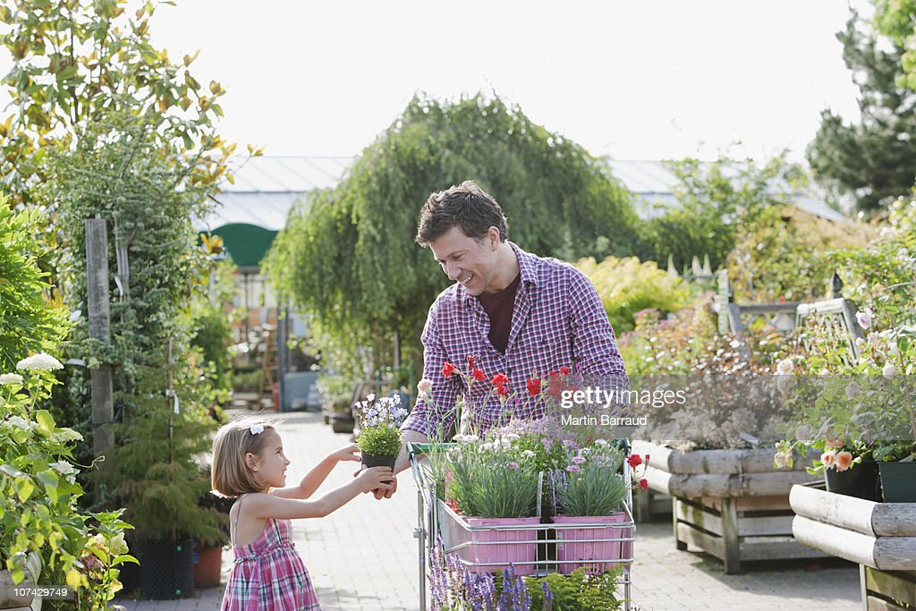 Father and daughter shopping together in nursery : Stock Photo