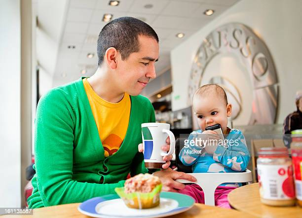 father and daughter (0-11 months) sitting at coffeehouse - 0 11 monate stock-fotos und bilder