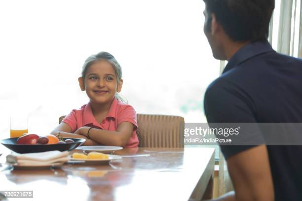 Father and daughter sitting at dinning table
