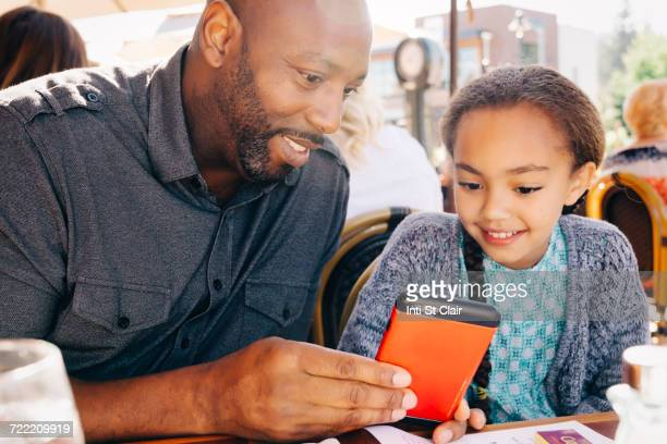 Father and daughter sitting at restaurant table texting on cell phone