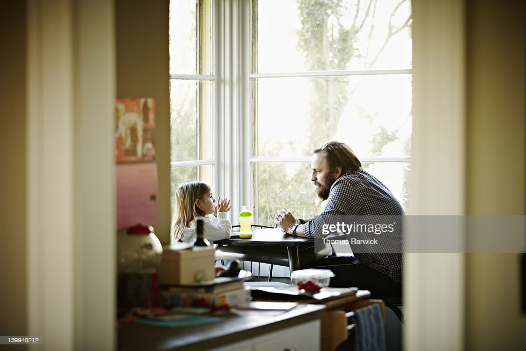 Father and daughter sitting at table in discussion : Stock Photo
