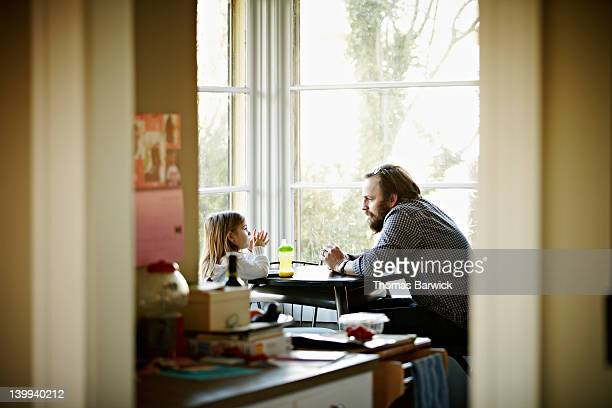 father and daughter sitting at table in discussion - daughter stock pictures, royalty-free photos & images