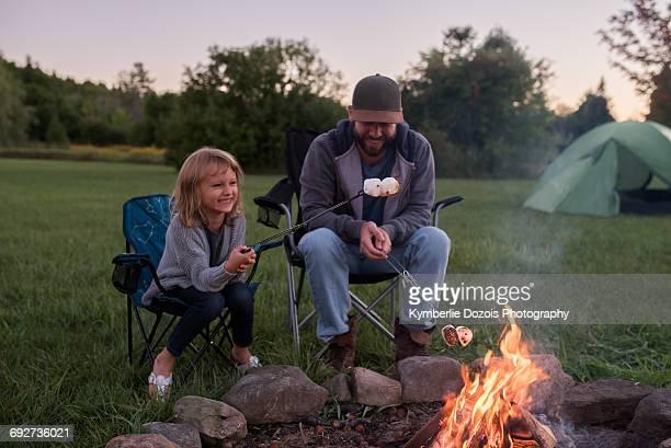 father and daughter sitting beside campfire, toasting marshmallows over fire - fuego al aire libre fotografías e imágenes de stock