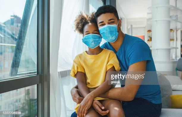 コロナウイルス検疫中に窓のそばに座っている父と娘。 - 片親 ストックフォトと画像