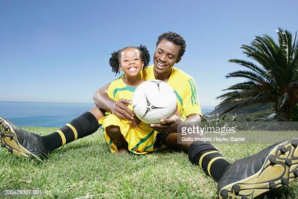 father and daughter (5-7) sitting by coast holding football, smiling - fußballtrikot stock-fotos und bilder