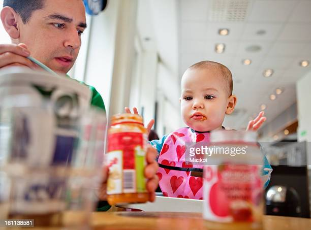 father and daughter (0-11 months) sitting by table - 0 11 monate stock-fotos und bilder