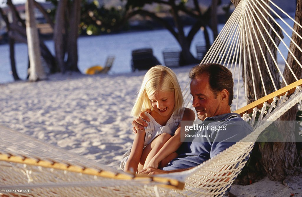 Father and daughter (6-7) sitting in hammock on beach : Stock Photo