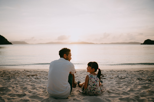 Father and daughter sitting on beach and looking at each other at sunset - gettyimageskorea