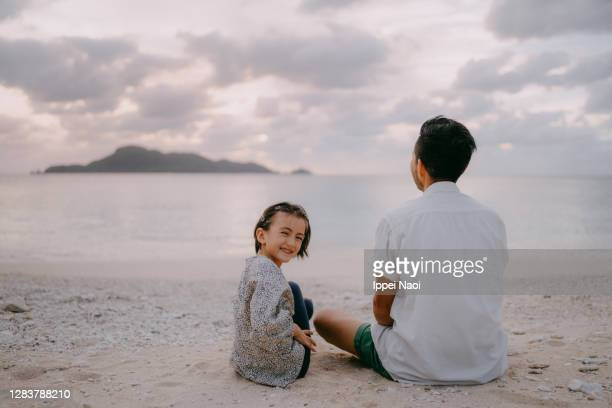 father and daughter sitting on beach at sunset - mid adult men stock pictures, royalty-free photos & images