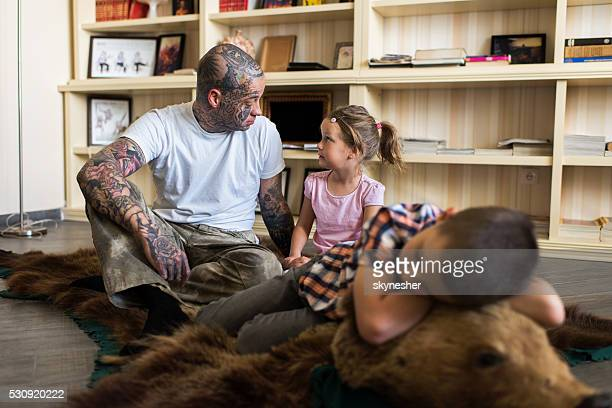 father and daughter sitting on bear skin rug and communicating. - animal skin rug stock pictures, royalty-free photos & images