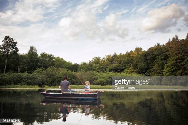 Father and daughter sitting on boat and fishing at lake