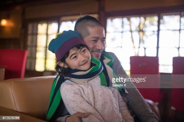 父と娘の椅子に一緒に座って、1 つのマフラーを身に着けています。
