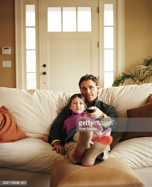 Father and daughter (4-6) sitting on couch, watching tv