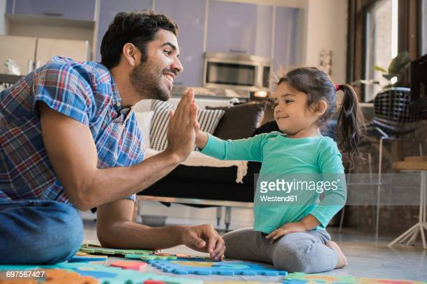 Father and daughter sitting on floor playing with childrens puzzle