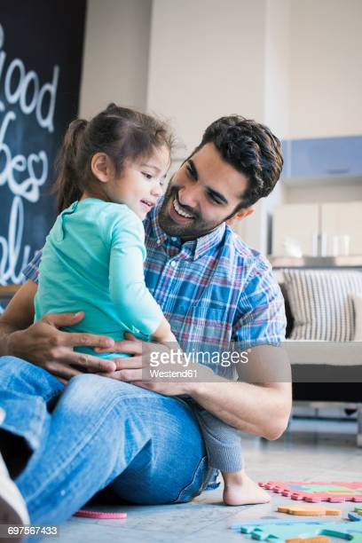 father and daughter sitting on floor playing with children's puzzle - 2 3 anni foto e immagini stock