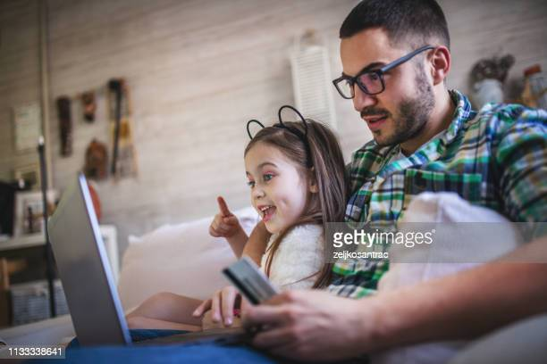 father and daughter  sitting on lounge sofa using laptop together - online shopping stock pictures, royalty-free photos & images