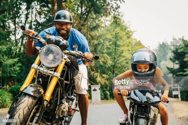 Father and daughter sitting on motorcycles
