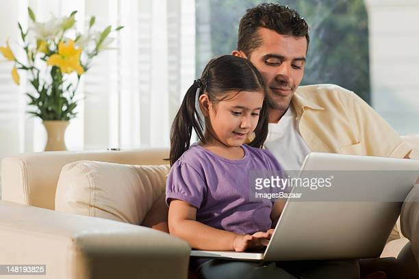 Father and daughter (6-7) sitting on sofa and using laptop