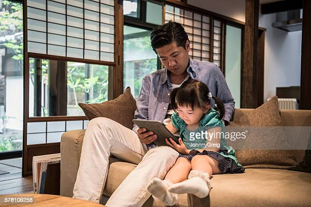 Father and daughter sitting on sofa using digital tablet