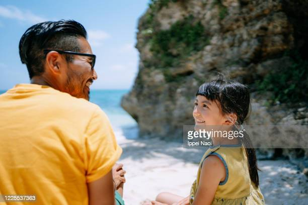 father and daughter sitting on tropical beach, okinawa, japan - ippei naoi stock pictures, royalty-free photos & images