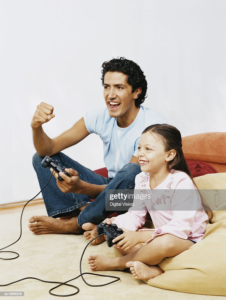 Father and Daughter Sitting Side by Side and Playing a Computer Game : Stock Photo