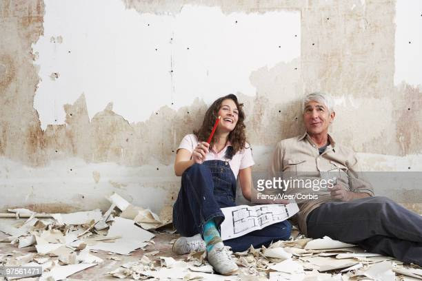 Father and daughter sitting together in unfinished room